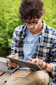 man in glasses with tablet pc computer outdoors