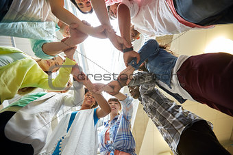 group of international students holding hands