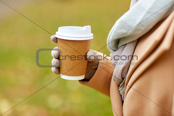 close up of woman with coffee in autumn park
