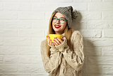 Smiling Hipster Girl in Winter Clothes with a Mug