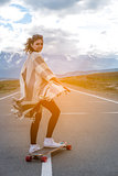Young cute girl rides skateboard on road in the mountains