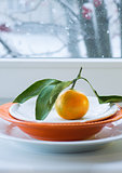 Tangerine with a branch and leaves on  plate against the background of  window  the snow