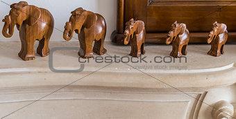 Carved wooden elephants on pedestal