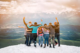 Group of friends are happy that climbed to the top  the mountain. They hug and jump. Looking into the distance with back  the camera.