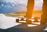 Longboard with athlete's foot is on the road in the mountains. Sunlight.
