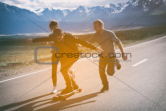 Group of friends run, laugh and having fun. The guy on longboard.