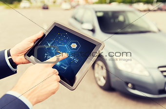close up of man with tablet pc diagnoses car