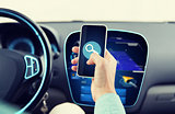 close up of man hand with smartphone driving car