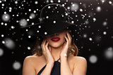 beautiful woman in black hat over snow