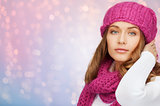 woman in hat and scarf over pink lights background