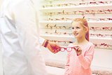 optician giving glasses to girl at optics store