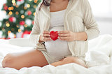 close up of pregnant woman with red heart in bed