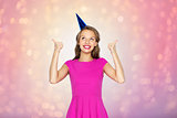 happy young woman or teen girl in party cap