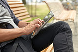 close up of man with tablet pc sitting on bench
