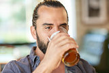 close up of man drinking beer at bar or pub