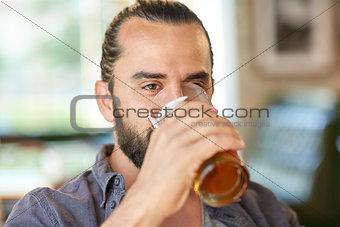 close up of man drinking beer at bar or pub