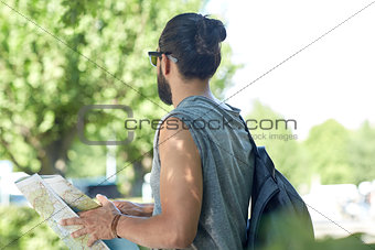 close up of man with backpack and map in city