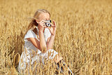 woman taking picture with camera in cereal field