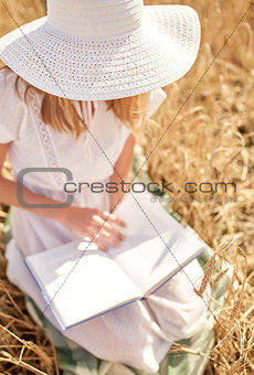 close up of woman reading book on cereal field