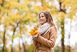 beautiful woman with maple leaves in autumn park