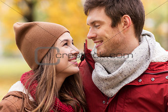 close up of happy couple walking in autumn park