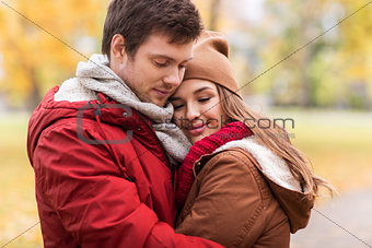close up of happy couple hugging in autumn park