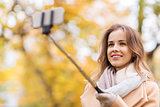 woman taking selfie by smartphone in autumn park
