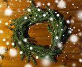 natural green fir branch wreath on wooden board