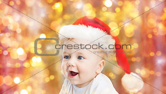 baby boy in christmas santa hat over blue lights