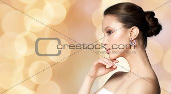 beautiful woman with earring over holidays lights