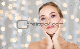 beautiful woman touching her face over lights