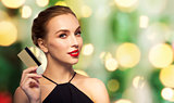 beautiful woman with credit card over black