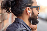 close up of man with earphones listening to music