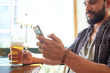 close up of man with smartphone and beer at pub