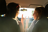 happy teenage girls or women driving in car