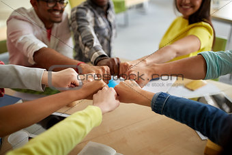 close up of international students hands fist bump