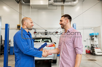 auto mechanic and man shaking hands at car shop