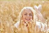happy woman or teen girl lying in cereal field