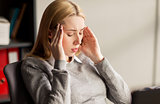 close up of businesswoman with headache at office