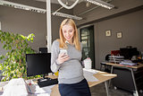 pregnant businesswoman with smartphone at office