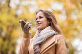 woman recording voice on smartphone in autumn park