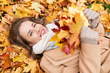 beautiful happy woman lying on autumn leaves