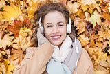 woman with headphones listening to music in autumn