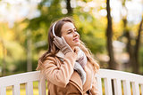 happy woman with headphones in autumn park