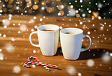 christmas candy canes and cups on wooden table
