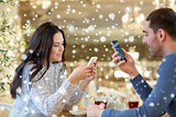 happy couple with smartphones drinking tea at cafe