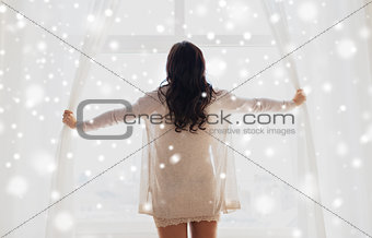 close up of happy woman opening window curtains