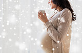 close up of pregnant woman with tea cup at window