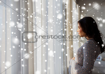 close up of happy pregnant woman looking to window