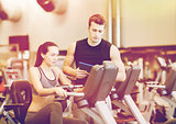 woman with trainer on exercise bike in gym